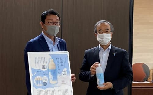 新発売の「お米ののむヨーグルト」を持つ花角知事㊨と葉葺氏(7月19日、新潟県庁)