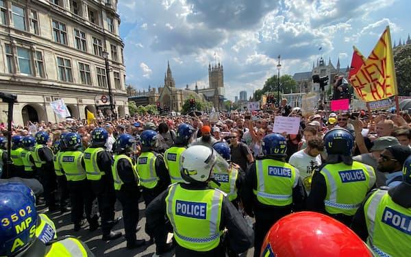 英ロンドンではロックダウン(都市封鎖)に反対する人々が警官隊とにらみ合いをしたが、封鎖の厳格さと感染者数や死者数との関係は解明されていない(7月)=ロイター