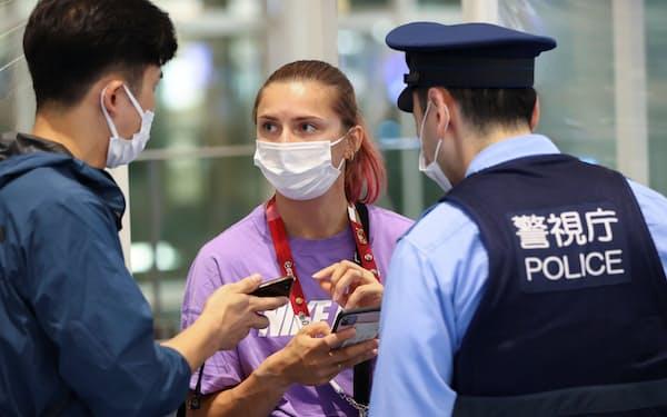1日、羽田空港で警察官と話すベラルーシのチマノウスカヤ選手(中)=ロイター