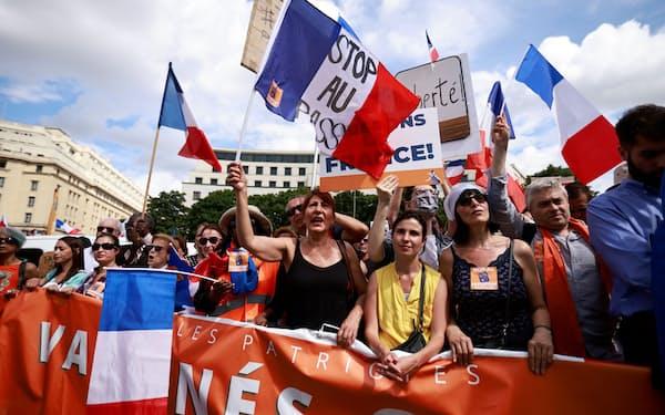 マクロン政権のコロナ対策に反発するデモ参加者(7月31日、パリ)=ロイター