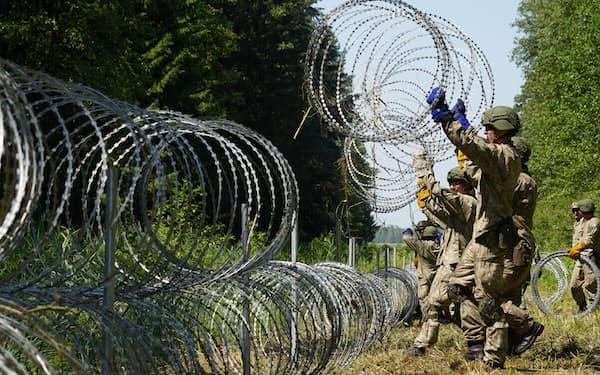 ベラルーシとの国境に有刺鉄線を設置するリトアニア兵=ロイター