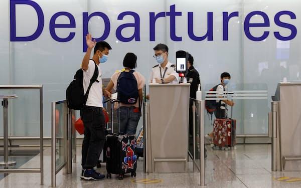 香港の国際空港で、家族に手を振り英国に渡航する男性(6月)=ロイター