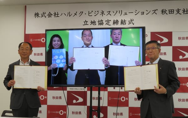 ハルメクHDの宮沢社長(中央)はリモート形式で記者会見に臨んだ(4日、秋田県庁)