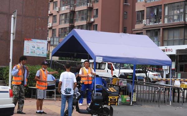 感染者が出て封鎖された団地。入り口で政府担当者らが監視する(4日、遼寧省大連市)