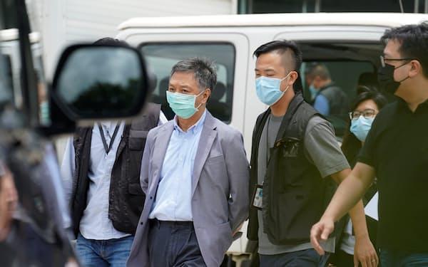 6月、アップル・デイリー幹部を国安法違反容疑で逮捕・連行する香港警察。民主派ジャーナリストへの弾圧が和らぐ気配はない=ロイター