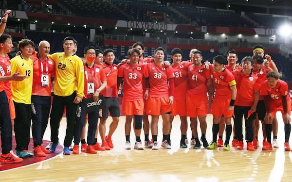1次リーグ最終戦のポルトガル戦で初勝利を挙げ、肩を組んで並ぶ土井(前列右から3人目)らハンドボール男子日本の選手ら=共同
