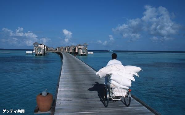 モルディブの宿泊施設に新しいタオルを届ける男性(2003年3月)=ゲッティ共同