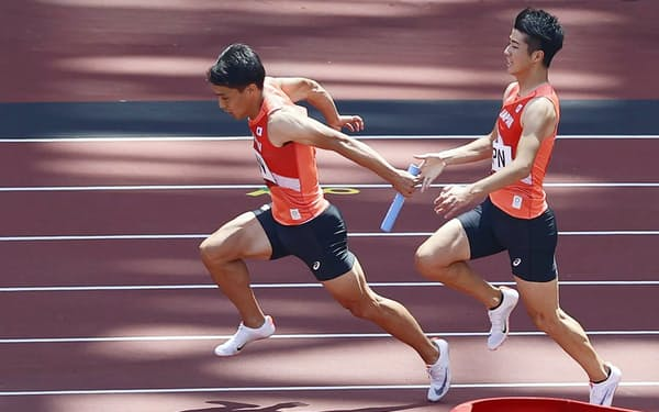 陸上男子400㍍リレー予選でバトンを受ける2走の山県(5日、国立競技場)