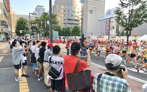 午前5時半の競技開始にもかかわらず、沿道には選手を一目見ようと観客が集まった(6日早朝、札幌市)
