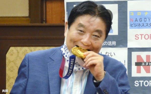 ソフトボール日本代表後藤希友選手の金メダルをかじる河村たかし名古屋市長(4日、名古屋市役所)=共同