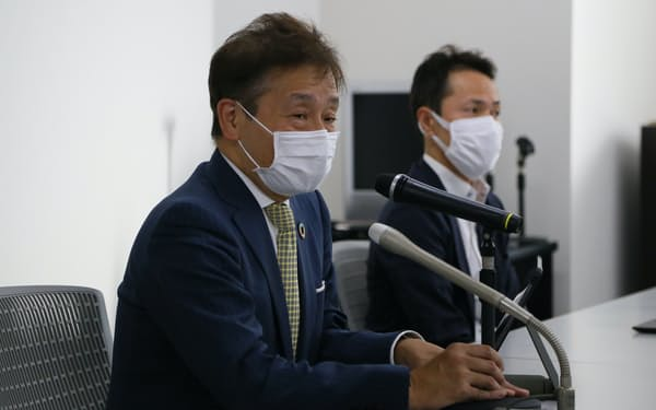 記者会見する堂島商取の中塚社長(左)=6日、東京都中央区