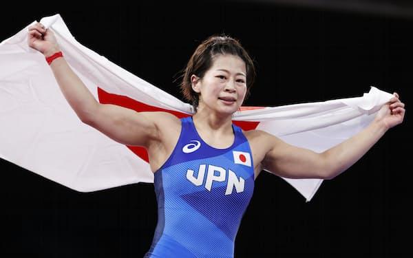 女子53キロ級で優勝し、日の丸を掲げ喜ぶ向田真優=共同