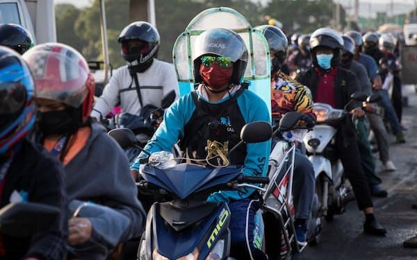 地域間のチェックポイントにはバイクで長蛇の列ができた(6日、マニラ首都圏)=ロイター