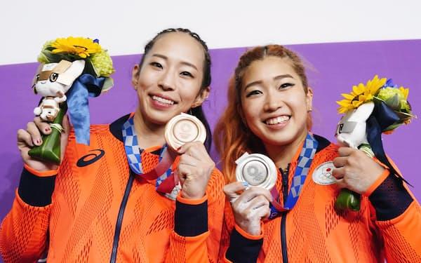スポーツクライミング女子複合のメダルを手に、笑顔の銀の野中生萌(右)と銅の野口啓代=共同