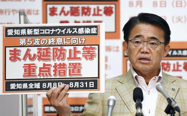 「まん延防止等重点措置」のボードを手に記者会見する愛知県の大村秀章知事(5日)=共同
