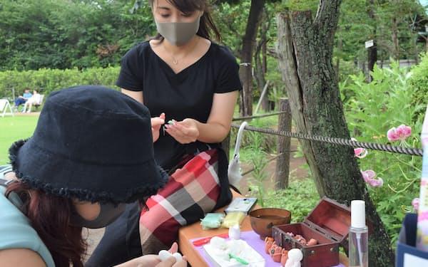公園で思い思いの人形をつくる鵜瀬さん(左)と城戸さん