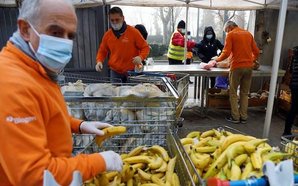 新型コロナにより経済的困難に陥った人々に食料を無料配給するミラノのボランティア団体。イタリアの貧困層人口は20年に前年比22%増え560万人に達した=ロイター