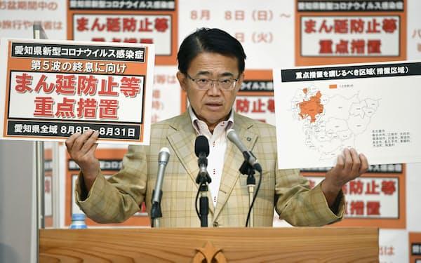 「まん延防止等重点措置」のボードを手に記者会見する愛知県の大村秀章知事=5日午後、愛知県庁