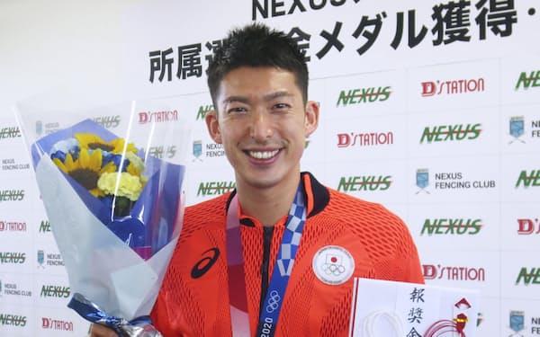 報奨金1億円の目録を手に笑顔のフェンシング男子エペ団体で金メダルを獲得した見延和靖(10日、群馬県高崎市)=共同