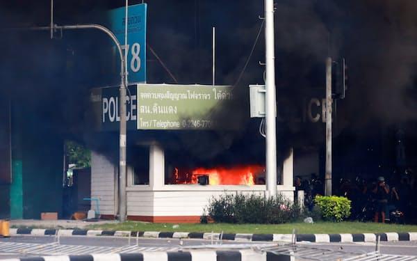 10日、タイ・バンコクのデモ現場で炎上した交番=ロイター