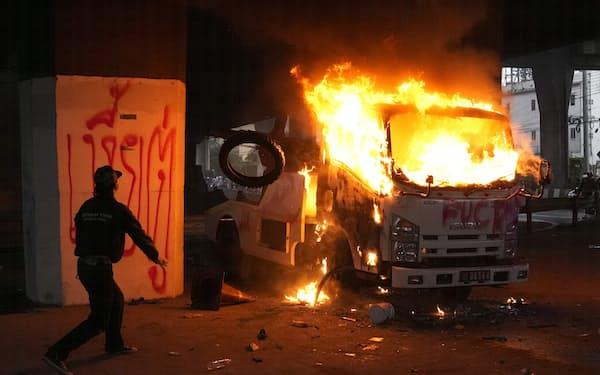 炎上する警察車両にタイヤを投げ込むデモ参加者(11日、バンコク)=AP