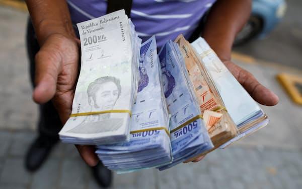 インフレで大量の紙幣を抱えるベネズエラ市民(5日、カラカス)=ロイター