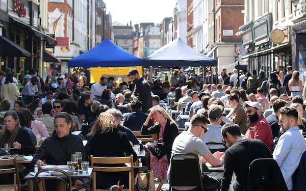 ロックダウン緩和でサービス業に活気が戻った(4月下旬、ロンドン中心部の繁華街)=ロイター