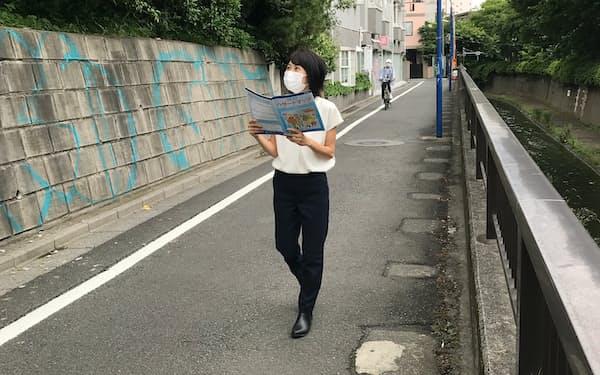 ハザードマップを手に歩きながら危険な場所を点検する奥村さん(東京都中野区)