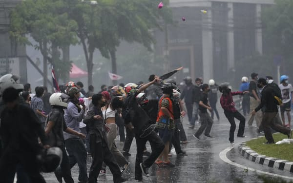 11日、タイ・バンコクで警官隊に物を投げつける反体制デモ隊=AP