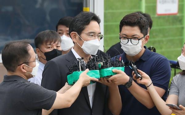 ソウル拘置所の正門前で取材に応じる李在鎔氏(中央、13日午前)=ロイター