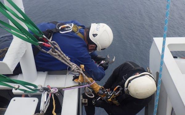 ロープアクセスで風車に登りメンテナンス作業をする