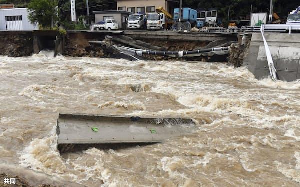 大雨の影響で増水した広島市安佐北区の鈴張川。後方は崩落した道路(13日午後)=共同