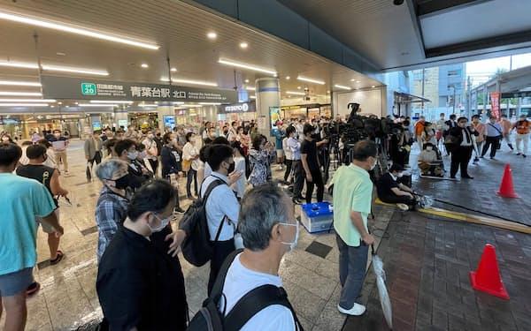 横浜市長選の候補者の第一声に耳を傾ける有権者(8日、横浜市)