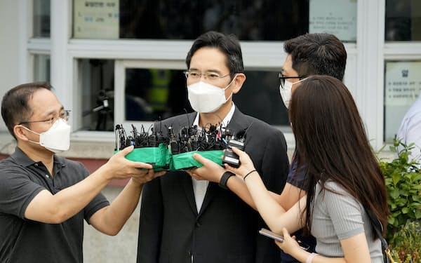李在鎔氏は30秒ほど立ち止まって報道陣の問いかけに応じた(13日午前、ソウル拘置所前)=AP