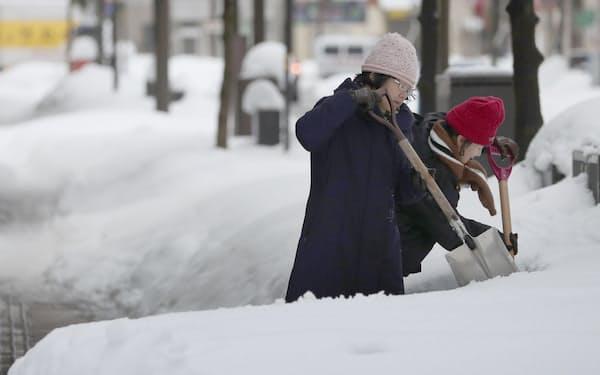 雪が積もった福井市内で雪かきをする人=11日午前8時