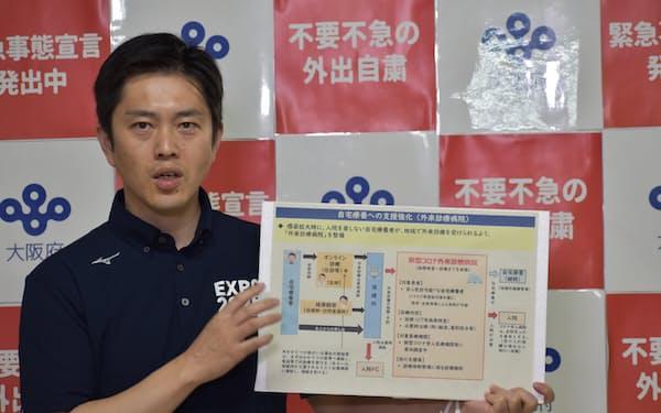 記者団の取材に応じる吉村知事(13日、大阪府庁)