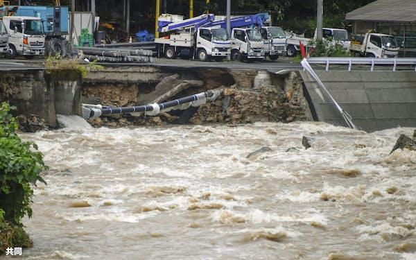 大雨の影響で増水した広島市安佐北区の鈴張川。後方は崩落した道路(13日午後1時21分)=共同