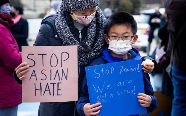 アジア系憎悪犯罪への抗議デモに参加する子供=ロイター