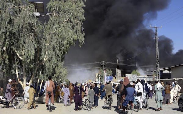 12日、アフガニスタン・カンダハルで、タリバンと治安部隊の戦闘で上がる煙=AP