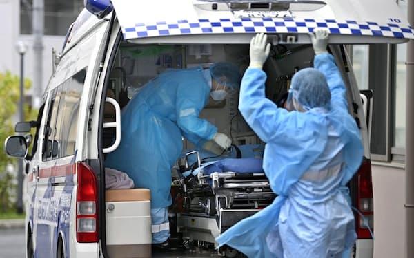 新型コロナウイルス患者を病院に搬送し、引き揚げるアンビュランスの救急救命士ら=共同