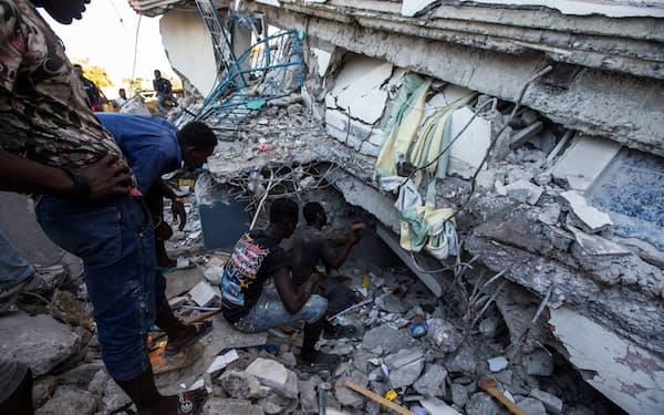 地震で倒壊した建物で捜索活動を続ける市民(14日、ハイチ西部レカイ)=ロイター