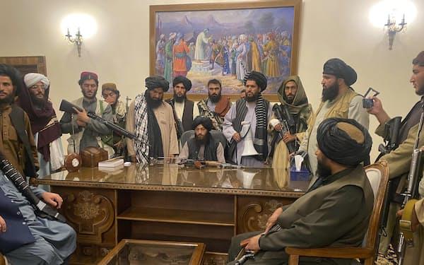 15日、カブールのアフガニスタン大統領府を占拠した反政府武装勢力タリバンの戦闘員ら=AP