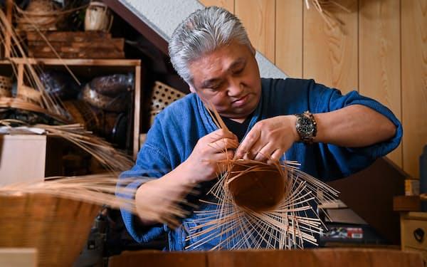 多くの工程を経て丁寧に下準備した竹を編み上げていく「籠師」の轡豊氏=大岡敦撮影
