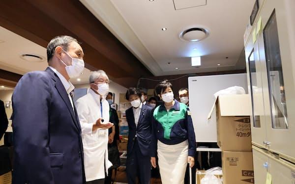 菅首相(左)と小池都知事(手前右)が療養施設を視察した(16日、東京・港)=内閣広報室提供