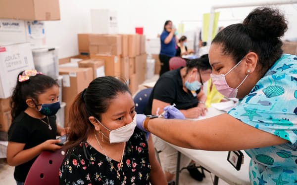 FILE - In this April 10, 2021, file photo, registered nurse Ashleigh Velasco, right, administers the Johnson & Johnson COVID-19 vaccine to Olga Perez at a clinic held by Healthcare Network, in Immokalee, Fla. With coronavirus shots now in the arms of nearly half of American adults, the parts of the U.S. that are excelling and those that are struggling with vaccinations are starting to look like the nation's political map: deeply divided between red and blue states. (AP Photo/Lynne Sladky, File)
