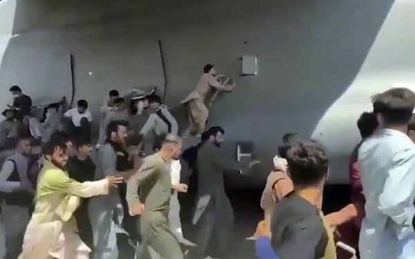 国際空港の滑走路を移動する米軍機と並走し、機体によじ登る市民ら(16日、カブール)=AP
