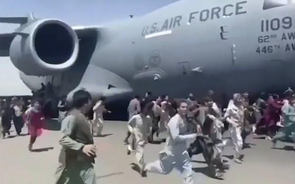 カブールの国際空港で米軍の輸送機と並走する人々=AP(16日)