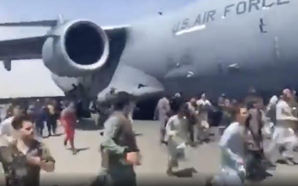 カブールの国際空港で、米軍機のそばを走るアフガン市民ら(16日、UGC提供)=AP
