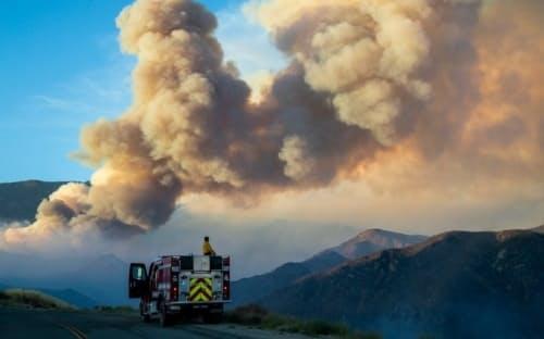 森林火災の煙には、危険な微小粒子状物質であるPM2.5という汚染物質が含まれており、そのせいで人が新型コロナに感染しやすくなる恐れがある。写真は、制御不能に陥った米カリフォルニア州チェリーバレーの火災「アップルファイア」の巨大な煙を見守る消防士。(PHOTOGRAPH BY GINA FERAZZI, LOS ANGELES TIMES/GETTY IMAGES)