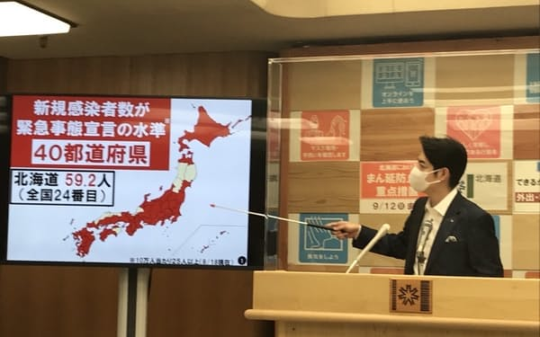 記者会見で全国の感染状況を説明する北海道の鈴木直道知事(19日、北海道庁)